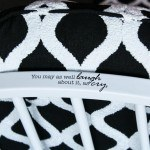 A closeup with a dry transfer saying on the arm of the chair.