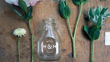 a product shot of a glass bottle with custom dry transfers