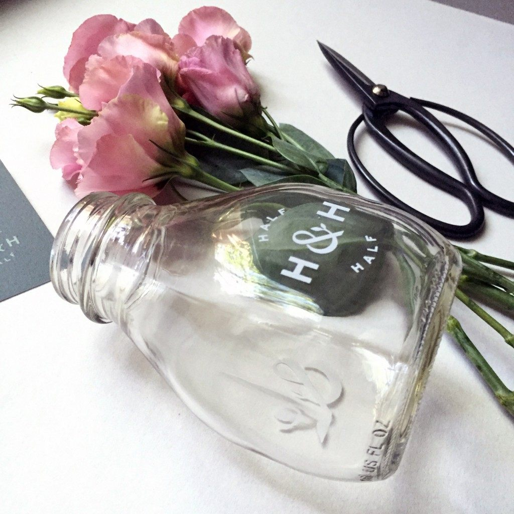 a closeup of flowers in a glass milk bottle prototype with a dry transfer of the logo on the front