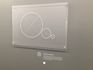 An artwork with a white description label beside it that's a custom dry transfer for walls.