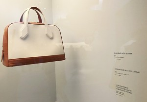 Vintage handbag with custom white exhibit label displaying a description of the artwork.