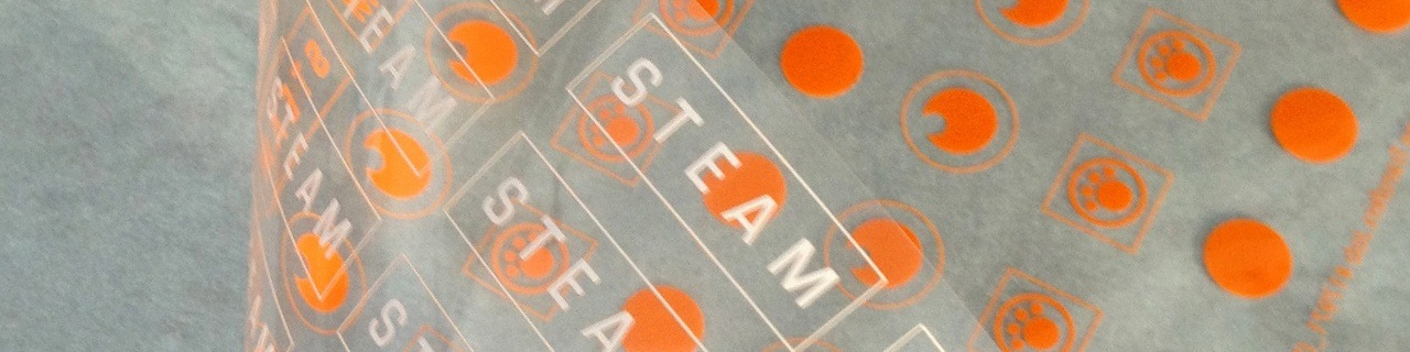 Custom dry transfer labels are affordable when ganged up on an individual dry transfer sheet. A close-up of rub-on labels in orange.