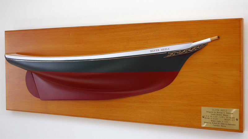A side view of a replica model boat built by Classic Yacht Models mounted on a wall plaque, gold foil transfers are used as decals.