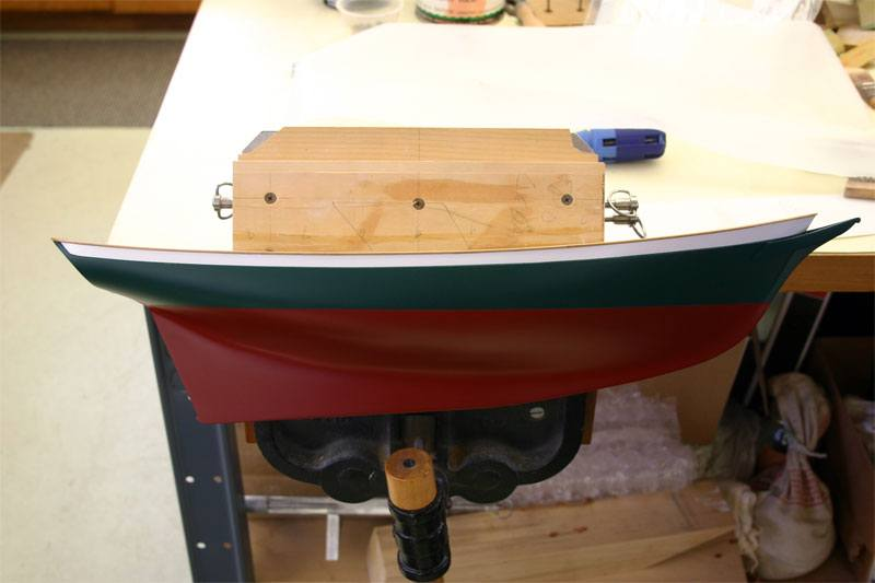 A photo of the replica model boat being built, the model is freshly painted and clamped onto the work bench before the custom transfer decals are applied.