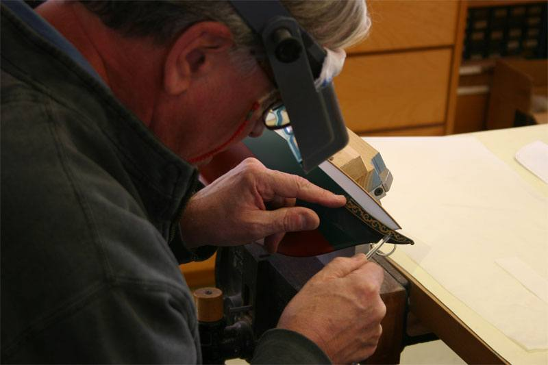 A classic model boat builder is rubbing down a custom gold colored foil transfer with a burnishing tool onto the bow of the replica model yacht.