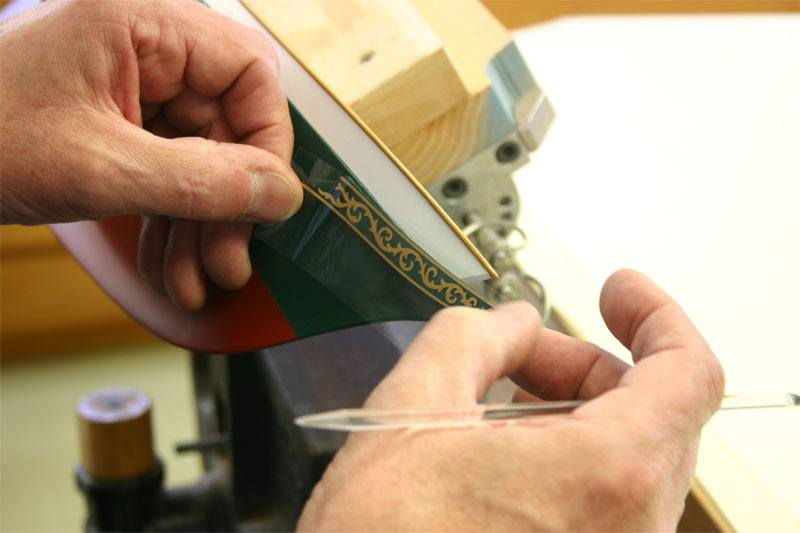 The model maker is finsihed rubbing the transfer and is now peeling the protective plastic off of the rubdown.