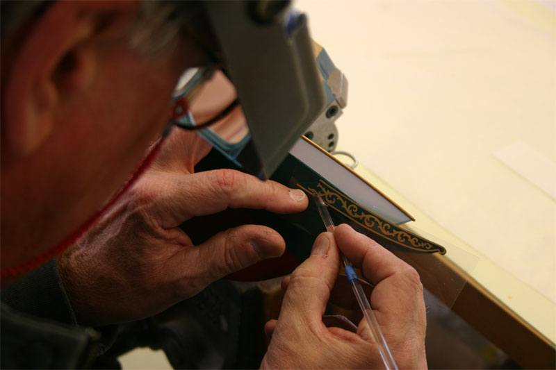 The model boat maker is using a burnishing tool to rub across the surface of the transfer to ensure smooth application.