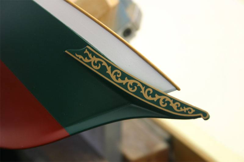 A closup photo of the bow of the model yacht showing the detail of the custom gold foil transfer they ordered.