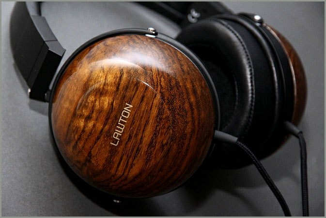 A product photo of headphones by Lawton Audio, which use a custom dry transfer on wood headphones showing their company logo.