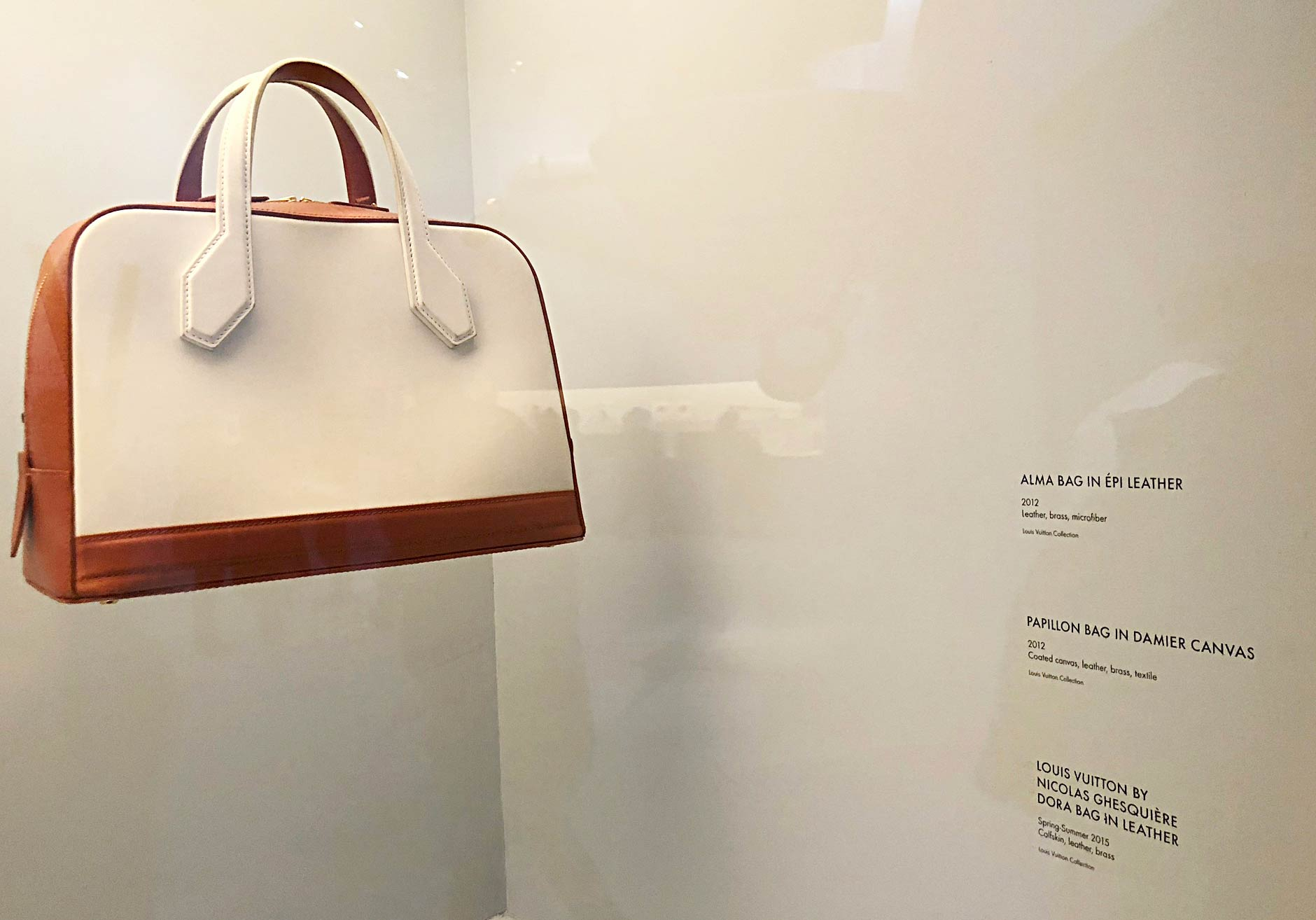 Louis Vuitton - Volez, Voguez, Voyagez exhibit, New York, NY. A leather, brass and microfiber handbag with cream-colored leather and light-auburn bottom and sides. Custom dry transfers are applied to the wall and used as descriptions for the piece.