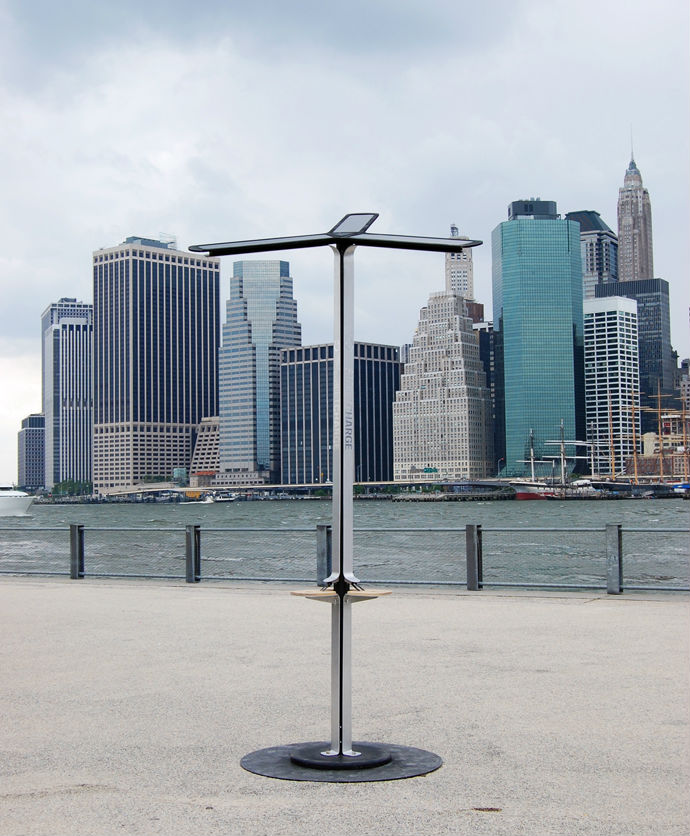 A photo of the StreetCharge solar phone charging station overlooking the cityscape of New York City. Overview of product prototype in public.