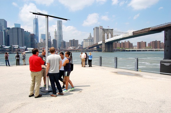 Promotional product photo showing people charging their phones at the StreetCharge phone battery recharging station on display in Brooklyn overlooking the Manhattan skyline.