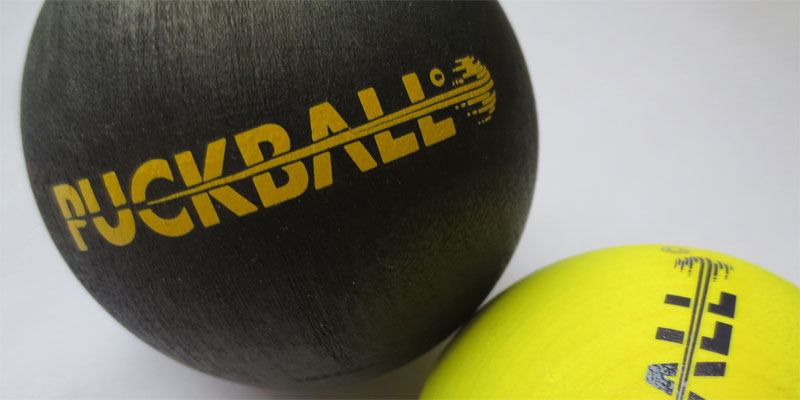 Two PuckBall balls in a photomontage that displays the new product branding.